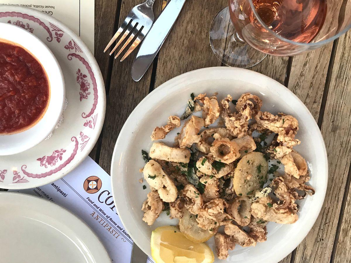 Fried calamari with lemon, marinara sauce, and a glass of rosé
