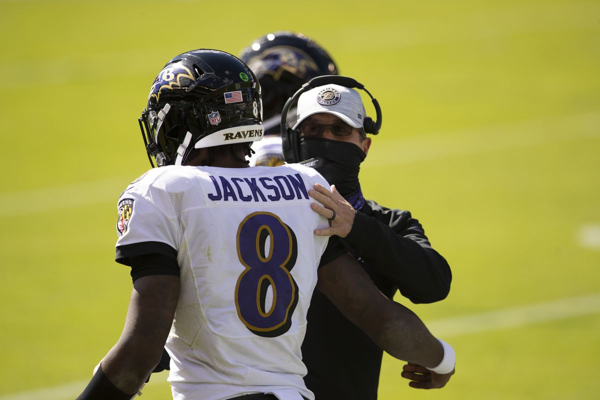 Lamar Jackson #8 is congratulated by head coach John Harbaugh after throwing a touchdown pass against the Philadelphia Eagles during the first quarter at Lincoln Financial Field on October 18, 2020 in Philadelphia, Pennsylvania.