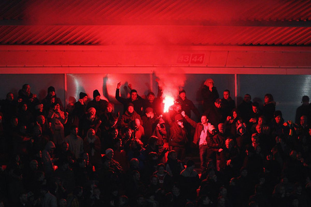 SOUTHAMPTON ENGLAND - JANUARY 29: A flare is lit by fans during the FA Cup sponsored by E.ON 4th Round match between Southampton and Manchester United at St Mary's Stadium on January 29 2011 in Southampton England.  (Photo by Clive Rose/Getty Images)