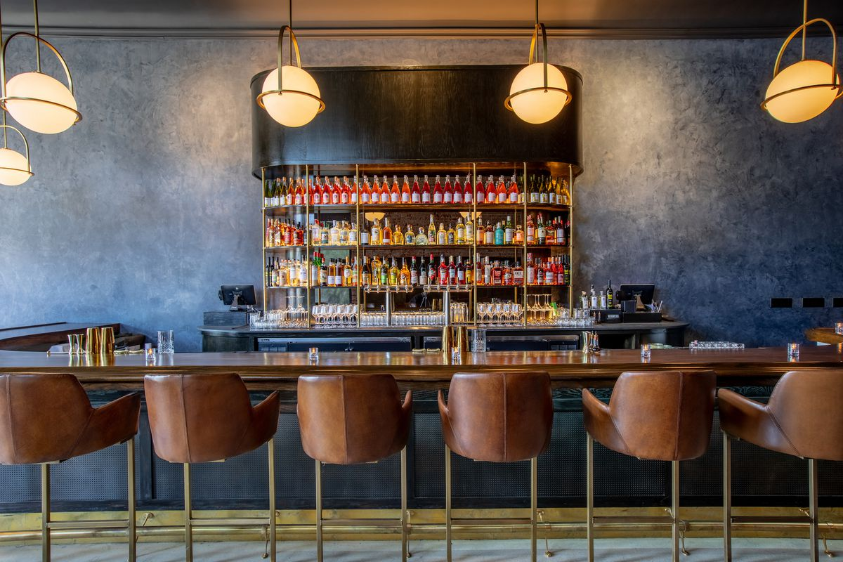 Leather bar seats and lots of bottles at a tall new bar with high ceilings.