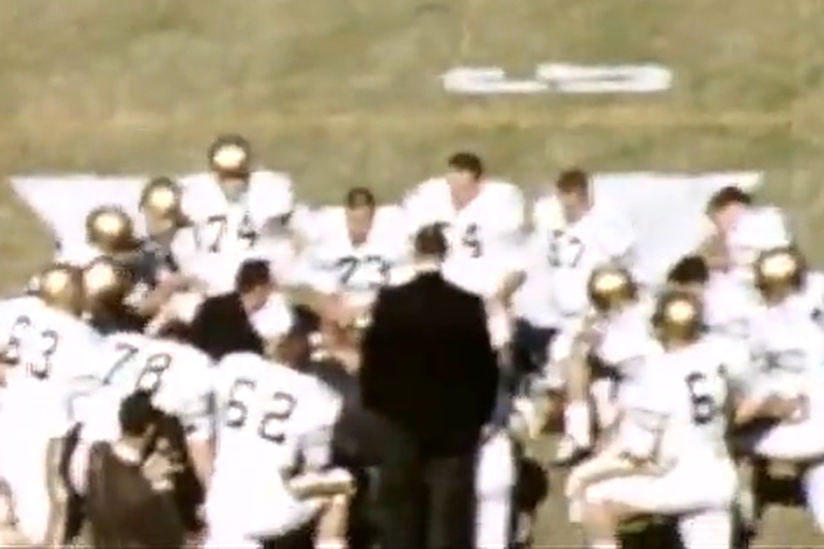 The Jacket offense huddles before the 1961 Gator Bowl.The big-eared man with his back to the camera is Bobby Dodd.
