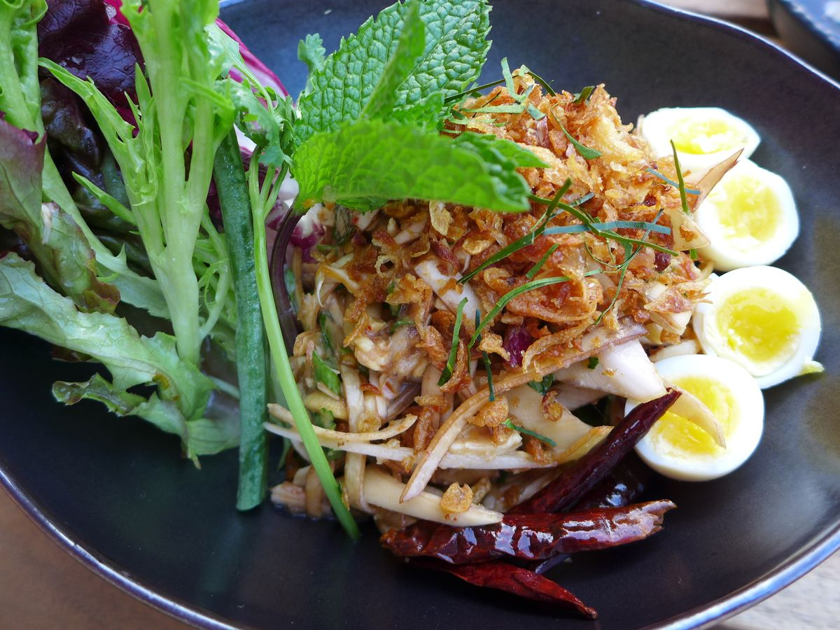 A dark oblong bowl with a jumble of julienne ingredients sided with boiled quail eggs and greens.