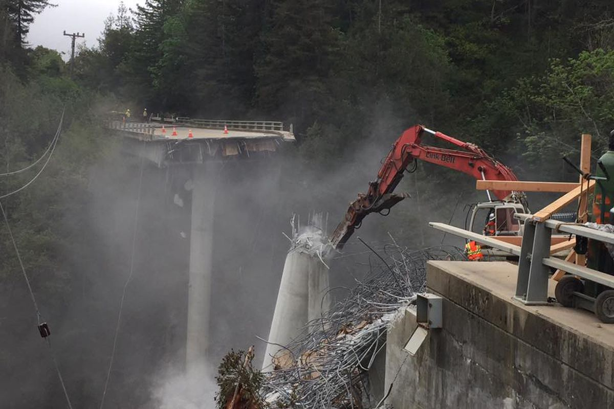A crane standing at the edge of a recently collapsed canyon bridge.