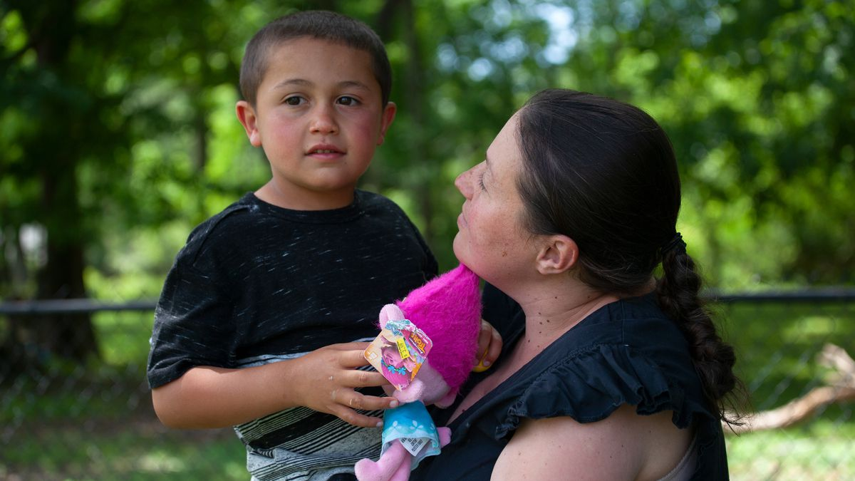 Anna Fridman holds her 5-year-old autistic son, Danny, who was out of school with his two brothers during the coronavirus outbreak, June 17, 2020.