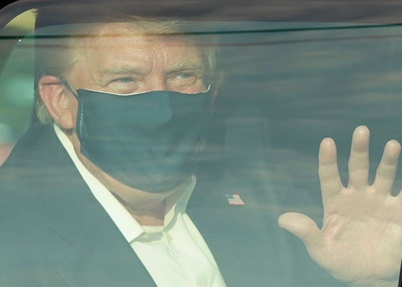 A masked Donald Trump waves from inside a vehicle