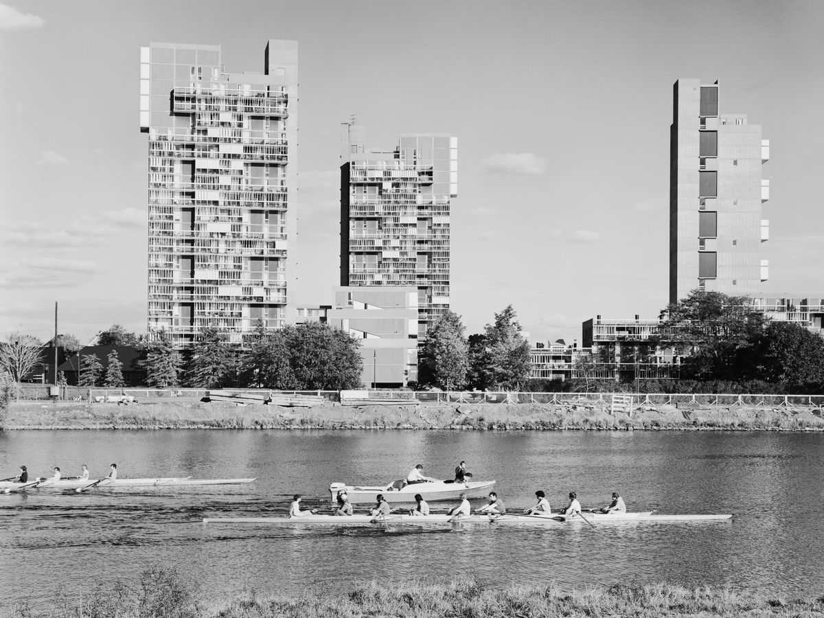 In the foreground is a body of water with people in row boats. In the distance are city buildings.