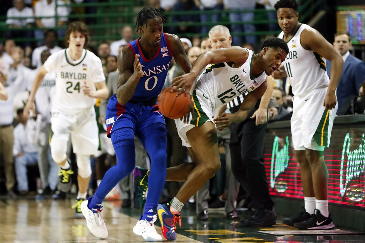 Baylor Bears guard Jared Butler saves the ball from going out of bounds as Kansas Jayhawks guard Marcus Garrett watches during the first half at Ferrell Center.