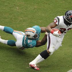 Miami Dolphins linebacker Cameron Wake (91) is dragged by Houston Texans running back Arian Foster (23) in the first quarter of an NFL football game on Sunday, Sept. 9, 2012, in Houston.