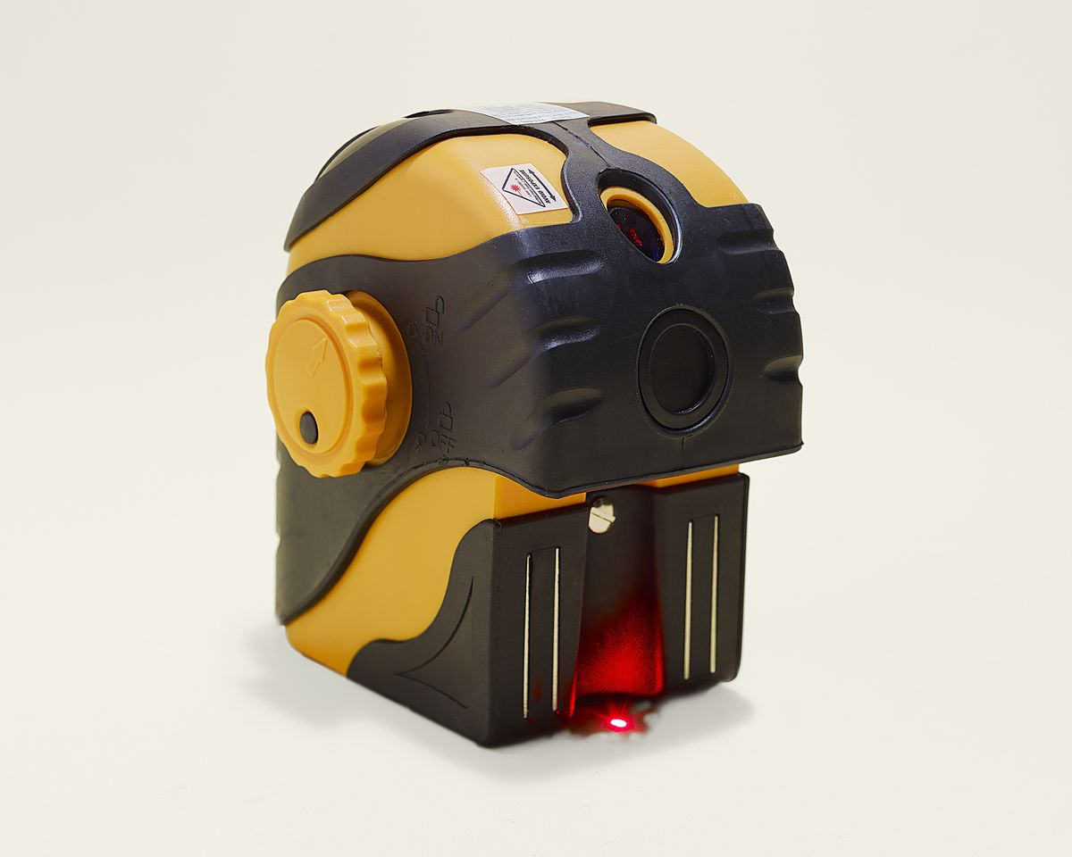 A plumb laser level with the beam pointing downwards and another pointing upwards on the front of the device.