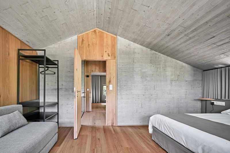 Bedroom clad in wood floors and concrete walls.