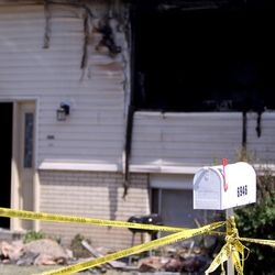 Police tape cordons off a home in West Valley City that caught fire early Monday, June 5, 2017. A woman was found dead following the early morning blaze.