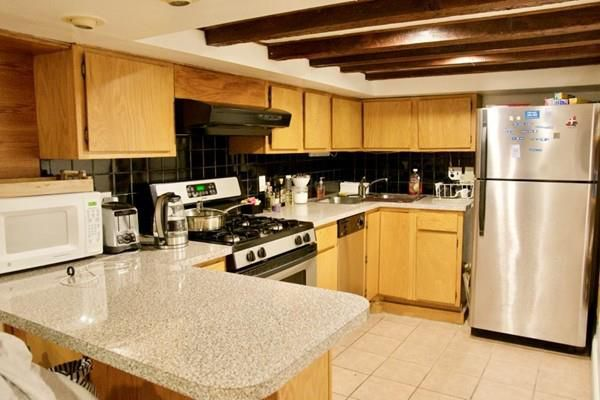 A kitchen with a U-shaped counter and a low ceiling.