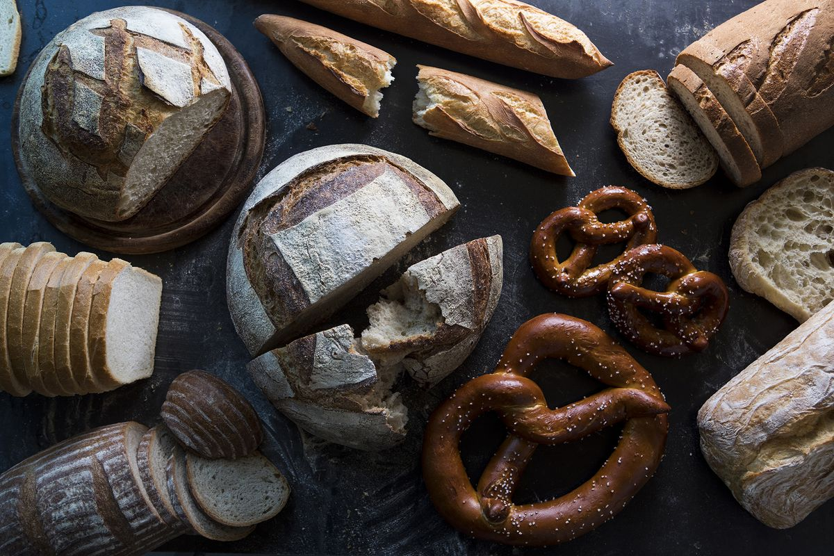 Overhead shot of different types of breads and pretzels on a black counter