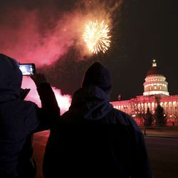 People watch fireworks over the Capitol in celebration of the 125th anniversary of Utah's statehood in Salt Lake City on Monday, Jan. 4, 2021.