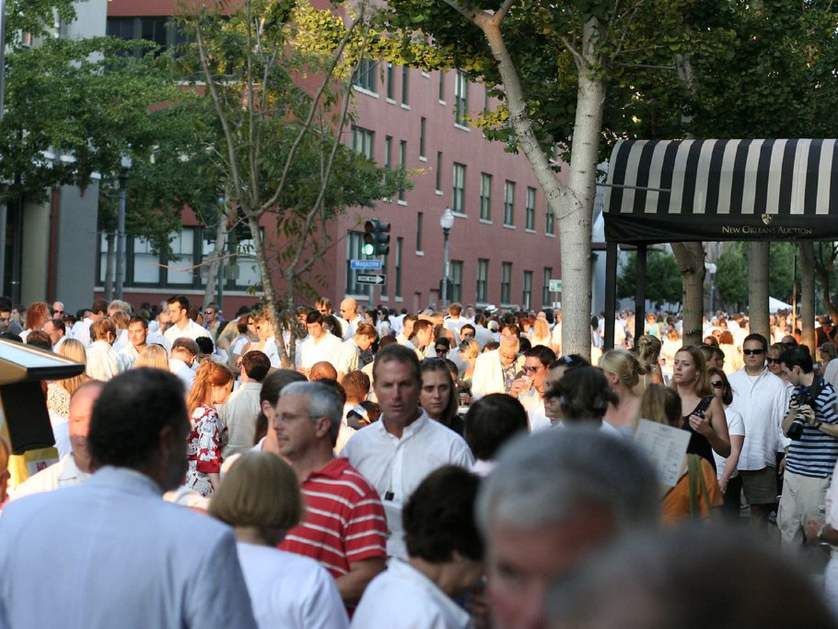 A large crowd of people wearing white flows through Julia Street in New Orleans.
