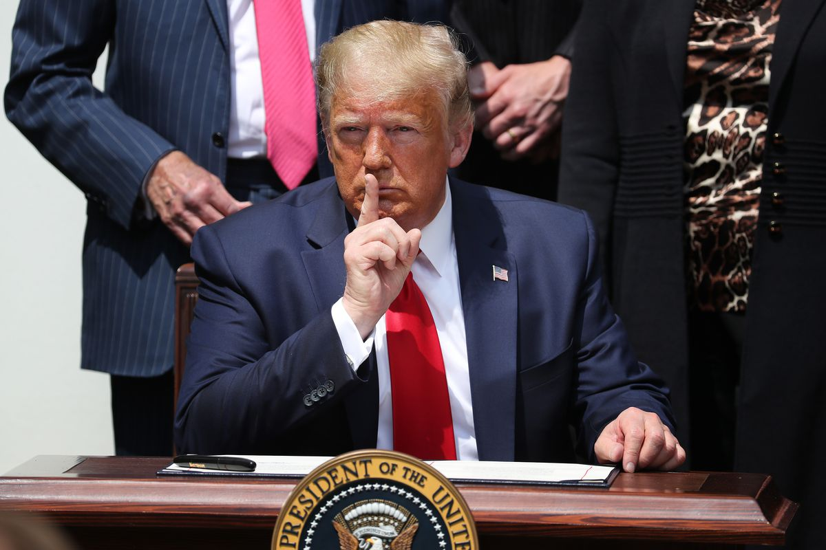 President Trump sitting at a desk holding his finger to his lips in a shushing gesture.