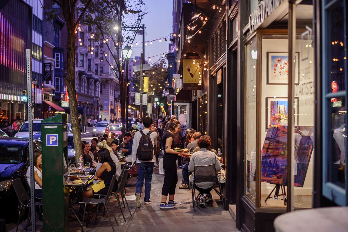 sidewalk crowded with outdoor tables in front of restaurant at night