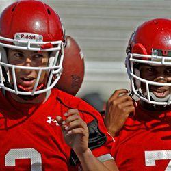 Utah quarterbacks Jordan Wynn, left, and Terrance Cain take their turn during Monday's practice.