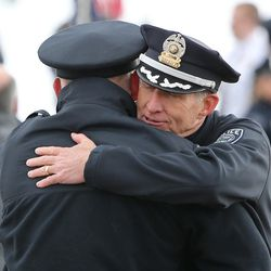 Salt Lake County Sheriff Jim Winder hugs a fellow officer at the graveside of Unified police officer Doug Barney, who was killed in the line of duty last week, at the Maverik Center on Monday, Jan. 25, 2016.