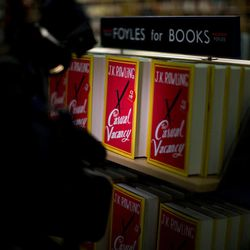"""A light from a video camera shines on copies of the """"The Casual Vacancy"""" by author J.K. Rowling displayed on shelves at a book store in London, Thursday, Sept. 27, 2012.  British bookshops are opening their doors early as Harry Potter author J.K. Rowling launches her long anticipated first book for adults.  Publishers have tried to keep details of the book under wraps ahead of its launch Thursday, but """"The Casual Vacancy"""" has gotten early buzz about references to sex and drugs that might be a tad mature for the youngest """"Potter"""" fans."""