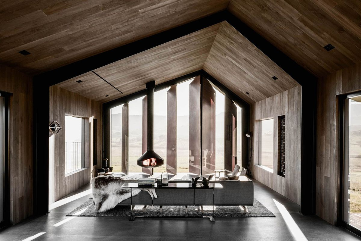 A living area with wooden walls, a sloped roof, and tall windows. There is a couch, chairs, and a fireplace.