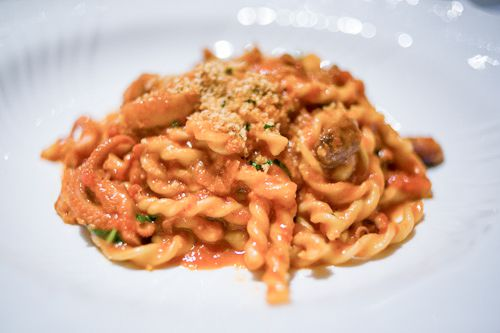 A white bowl with fusilli, red sauce, bone marrow, and octopus.
