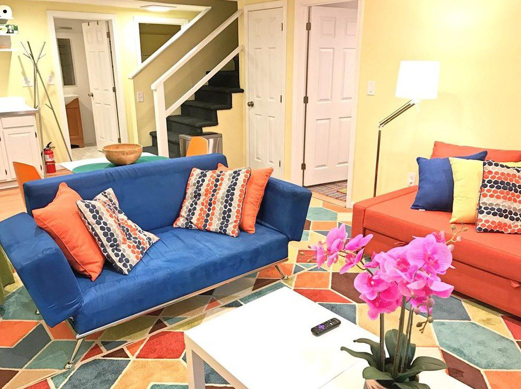A colorful living room with two couches and a stairway leading into the room.