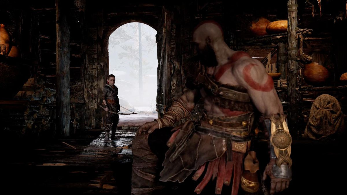 God of War - Kratos looks at Atreus standing by the door of their home