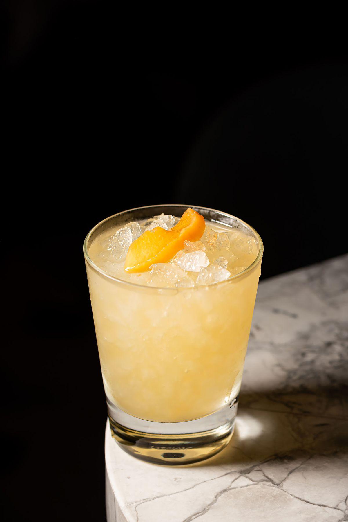 Oaxacan cocktail with mezcal espadin, reposado tequila, peach-habanero shrub, lemon, orange at Gigi's Hollywood in a glass.