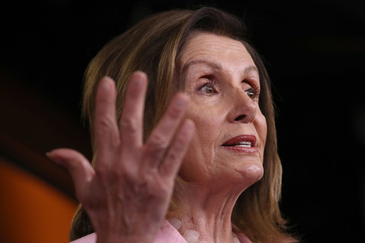 Pelosi gestures at a podium in a pink suit.