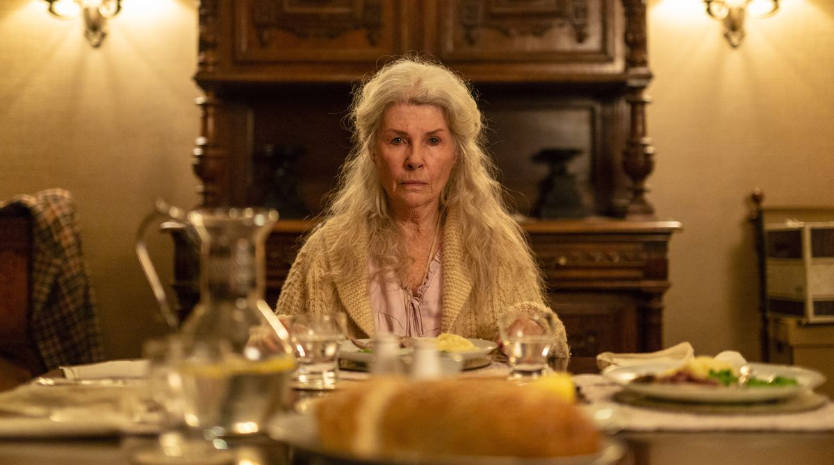 Robyn Nevin in Relic sits stone-faced at the dinner table, surrounded by untouched food.