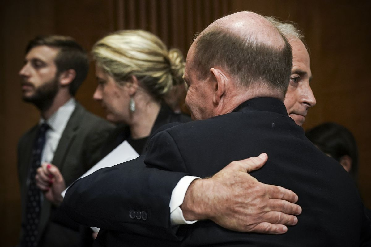 Sen. Bob Corker (R-TN), chairman of the Senate Foreign Relations Committee, hugs Sen. Chris Coons (D-DE) after approving the nomination of CIA Director Mike Pompeo to be Secretary of State, on April 23, 2018.