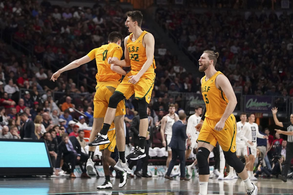 San Francisco Dons forward Remu Raitanen (11), forward Dzmitry Ryuny (22), and center Jimbo Lull (5) celebrate against the Gonzaga Bulldogs during the first half during the semifinal game in the WCC Basketball Championships at Orleans Arena.