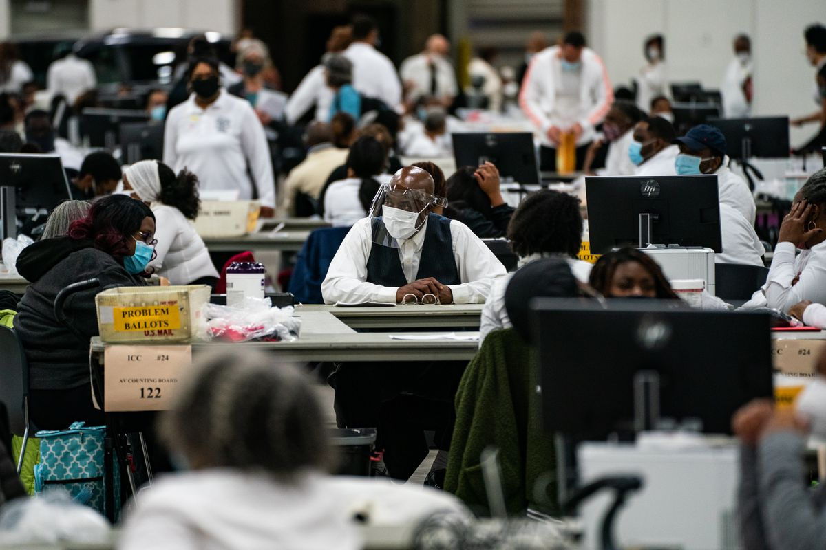 """A vast hall is filled with mostly Black workers in white shirts and black pants. They sit distanced at tables in PPE, covered in boxes and computers; one has a label facing the viewer that reads """"Problem Ballots."""""""