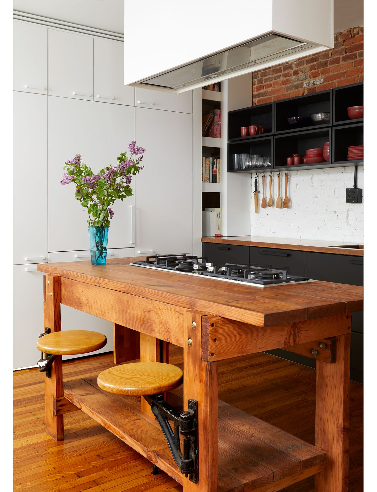A kitchen. There is a large wooden kitchen island with attached stools. One wall is a row of white storage cabinets. The other wall has black kitchen cabinetry. At the top of the wall is red exposed brick.