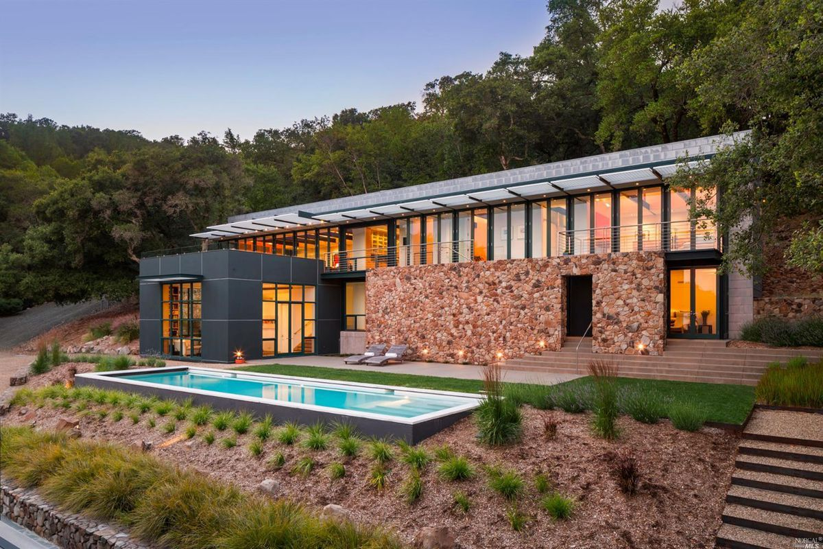 Rectilinear two-story home with walls of glass and stone, with swimming pool and surrounded by trees.