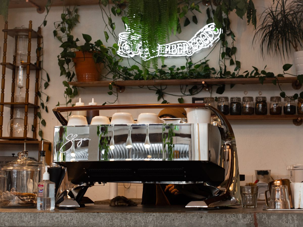 The interior of Ember Goods, with the name of the cafe is scripted bright neon and a giant Slayer espresso machine in the foreground