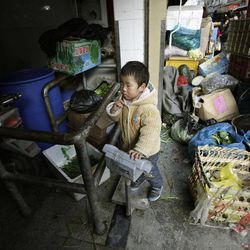 In this March 20, 2012 photo, a boy plays at the backside of a vegetable market in Shanghai, China. China's inflation edged up in March as the government shifted focus from containing politically dangerous price rises to stimulating its slowing economy. Consumer prices rose 3.6 percent over a year earlier, up from February's 3.2 percent, data showed Monday, April 9, 2012.