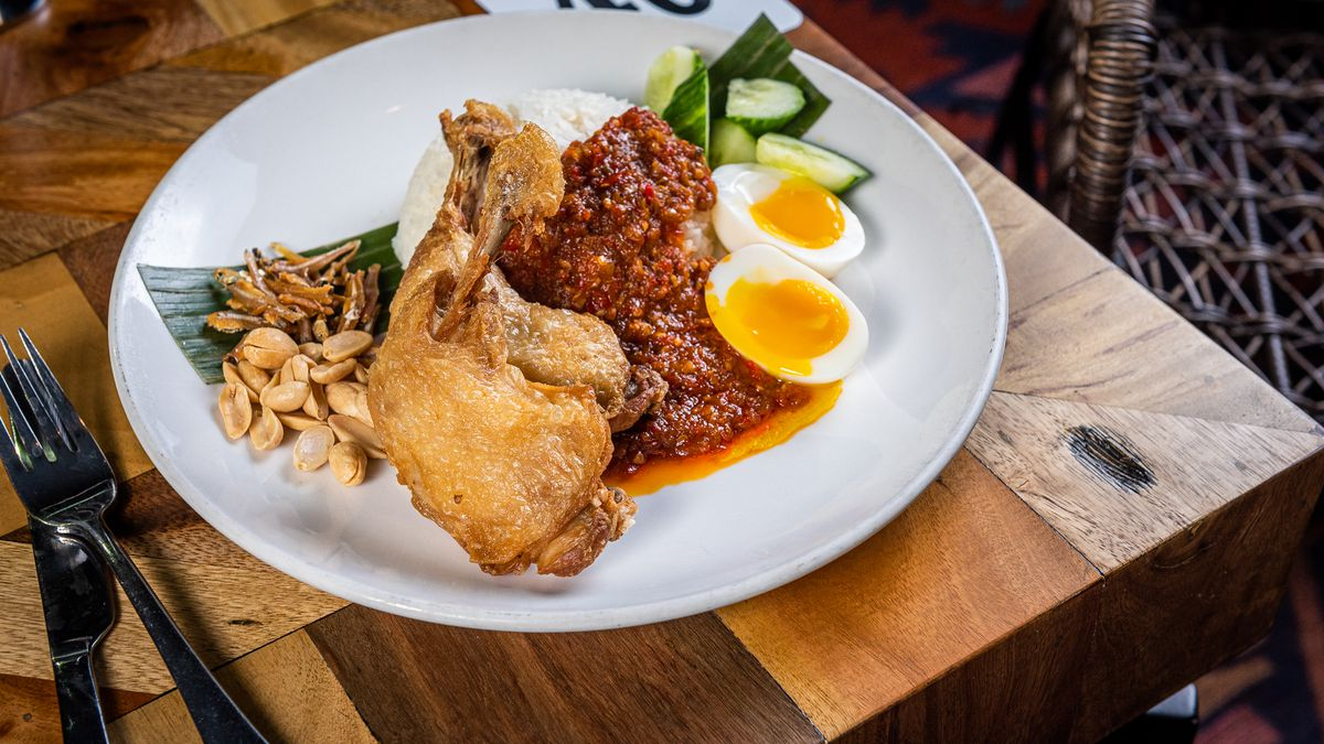Chicken nasi lemak from Makan with chef's sambal, peanuts, fried anchovies, cucumbers, and soft eggs.