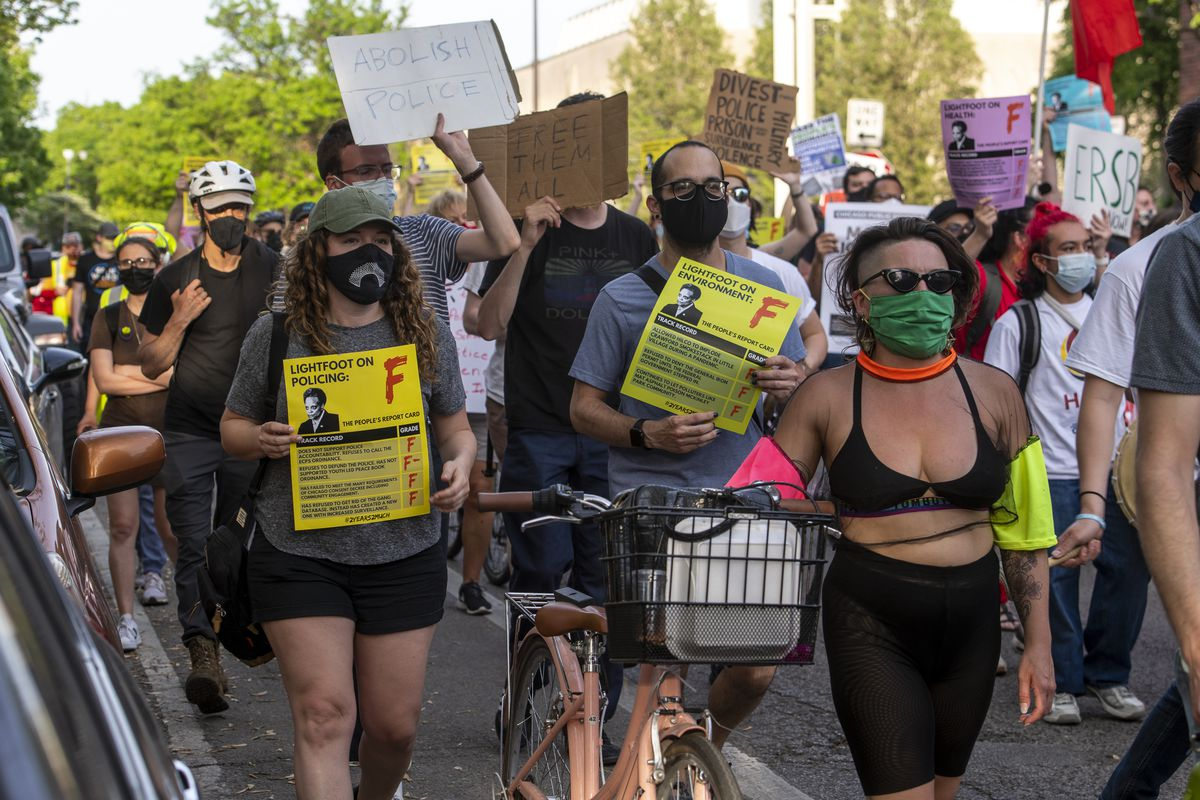 Protesters march down Wrightwood Avenue toward Mayor Lori Lightfoot's home in Logan Square on Thursday during a protest over Lightfoot's first two years in office.
