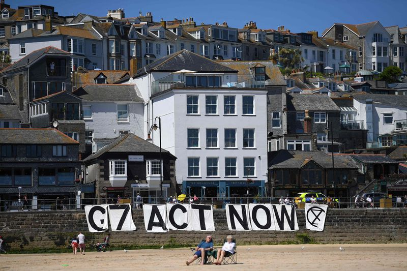 Extinction Rebellion environmental activists attach a banner calling on G7 leaders to act on climate change on the beach in St Ives, Cornwall during the G7 summit on Sunday.