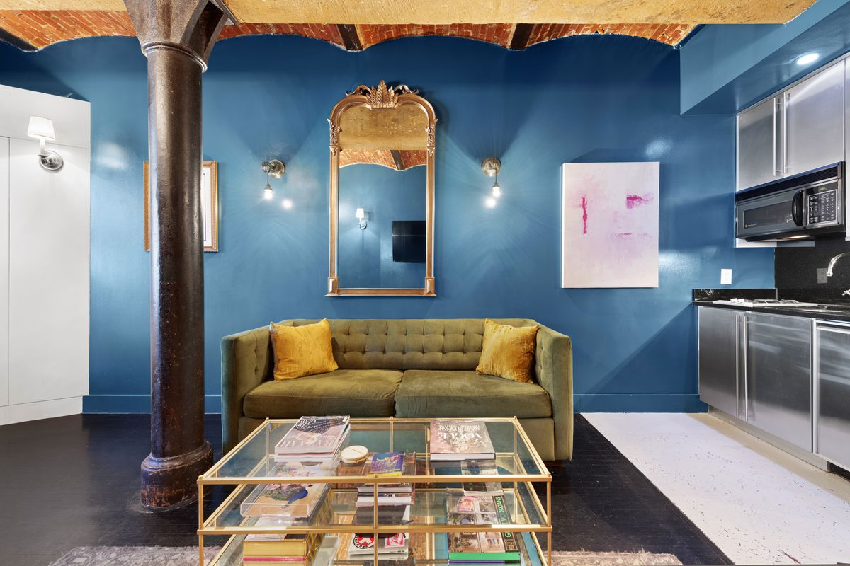 A living room with bright blue walls, vaulted ceilings, a green couch, exposed brick, and a brown column.