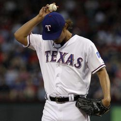 Texas Rangers' Yu Darvish adjust his cap between pitches in the third inning of a baseball game against the New York Yankees on Tuesday, April 24, 2012, in Arlington, Texas.