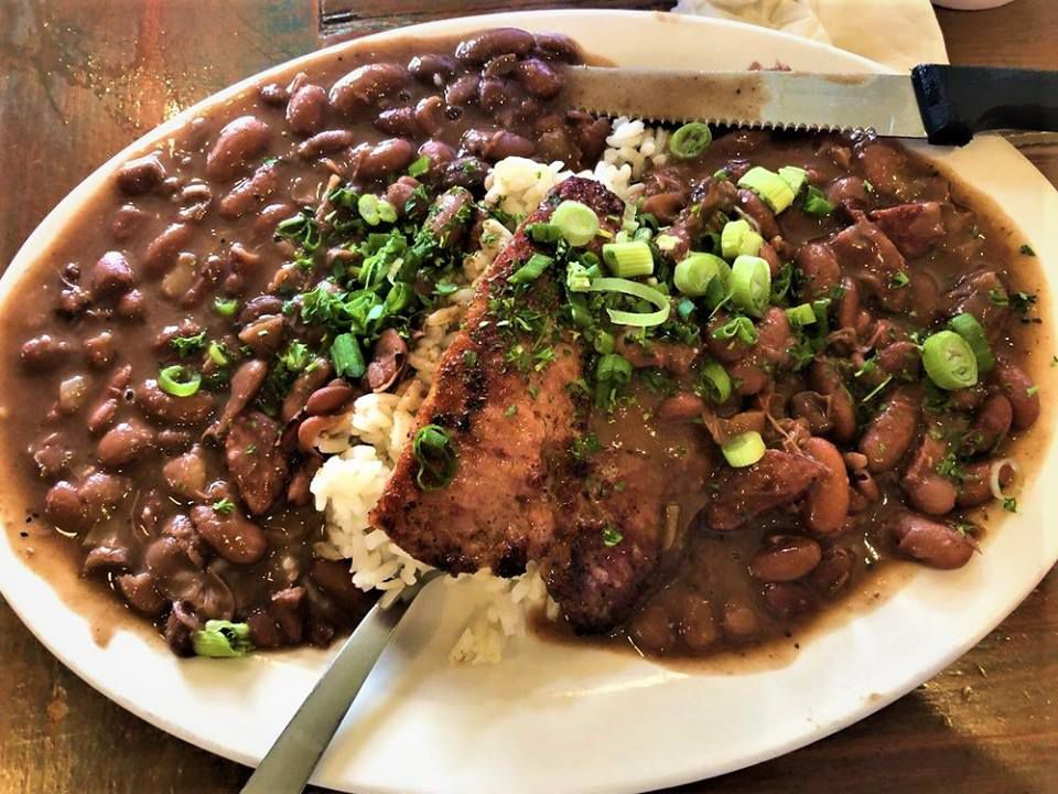 A plate of red beans served with rice and sausage, topped with parsley and green onion
