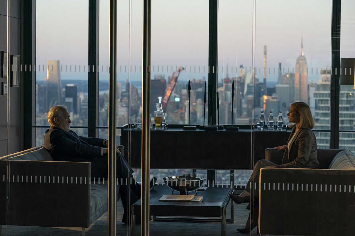 Logan and Shiv sit in a gorgeous office in the Waystar-Royco home base, framed against a New York skyline featuring the setting sun.