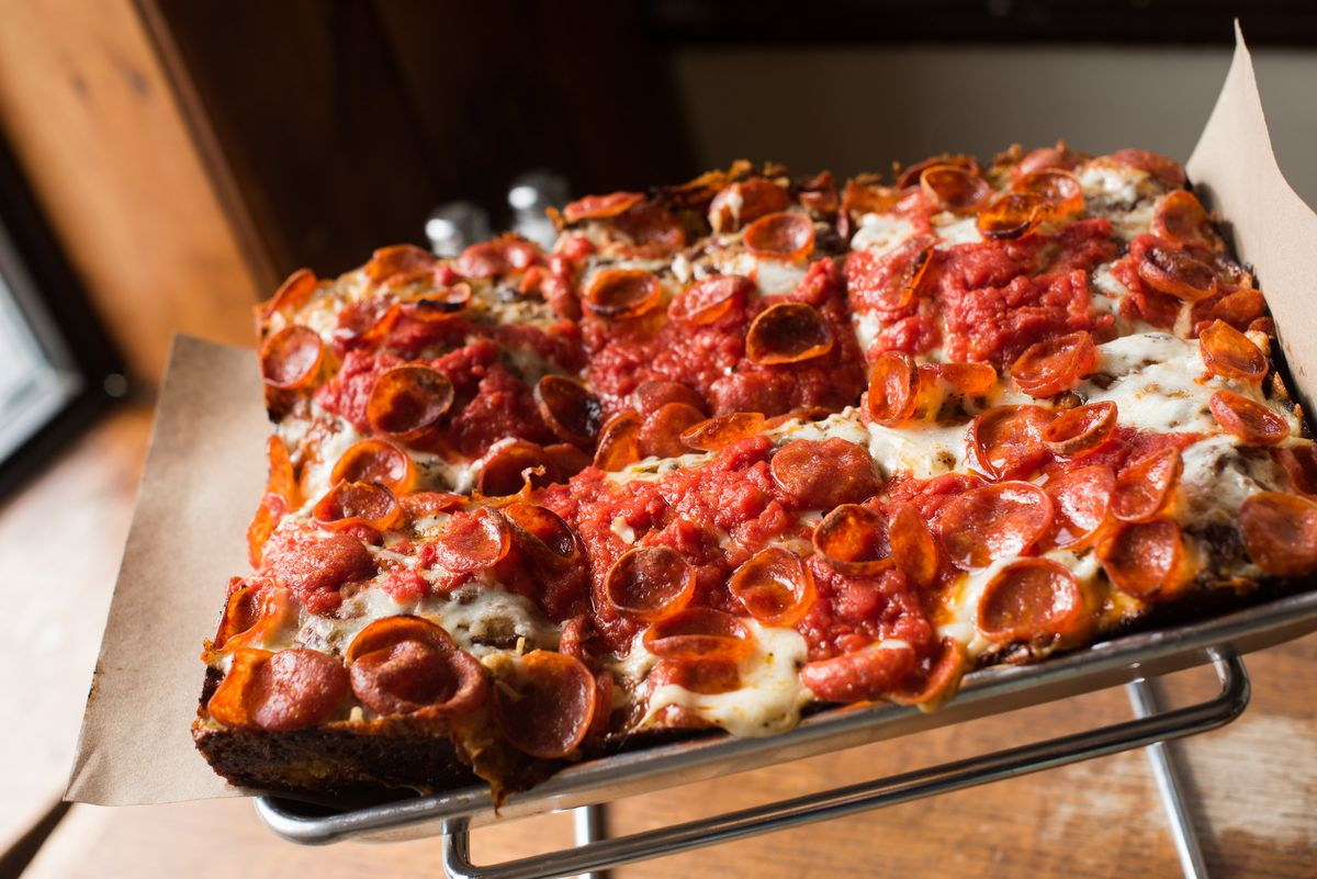Rectangular Detroit-style pizza, cut into six slices, is topped with pepperoni and served on a metal tray propped up on a metal stand