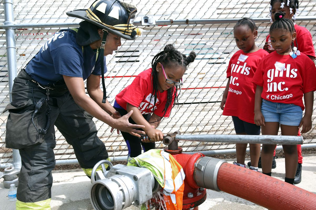 Firefighter Carla Lloyd directs Kimora on how to open a hydrant