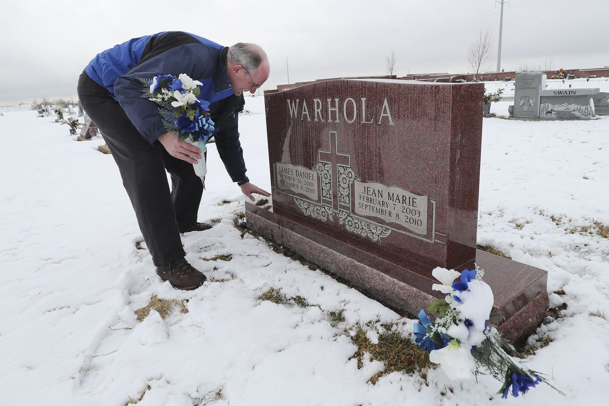 Ken Warhola cleans the headstone marking the graves of his children, James, 8, and Jean Marie, 7, at Lindquist Memorial Park in Layton on Wednesday, Jan. 29, 2020. Prosecutors say the children were strangled by their mother more than nine years ago. On Wednesday, Ken Warhola said is doesn't want to see a plea deal in the case.