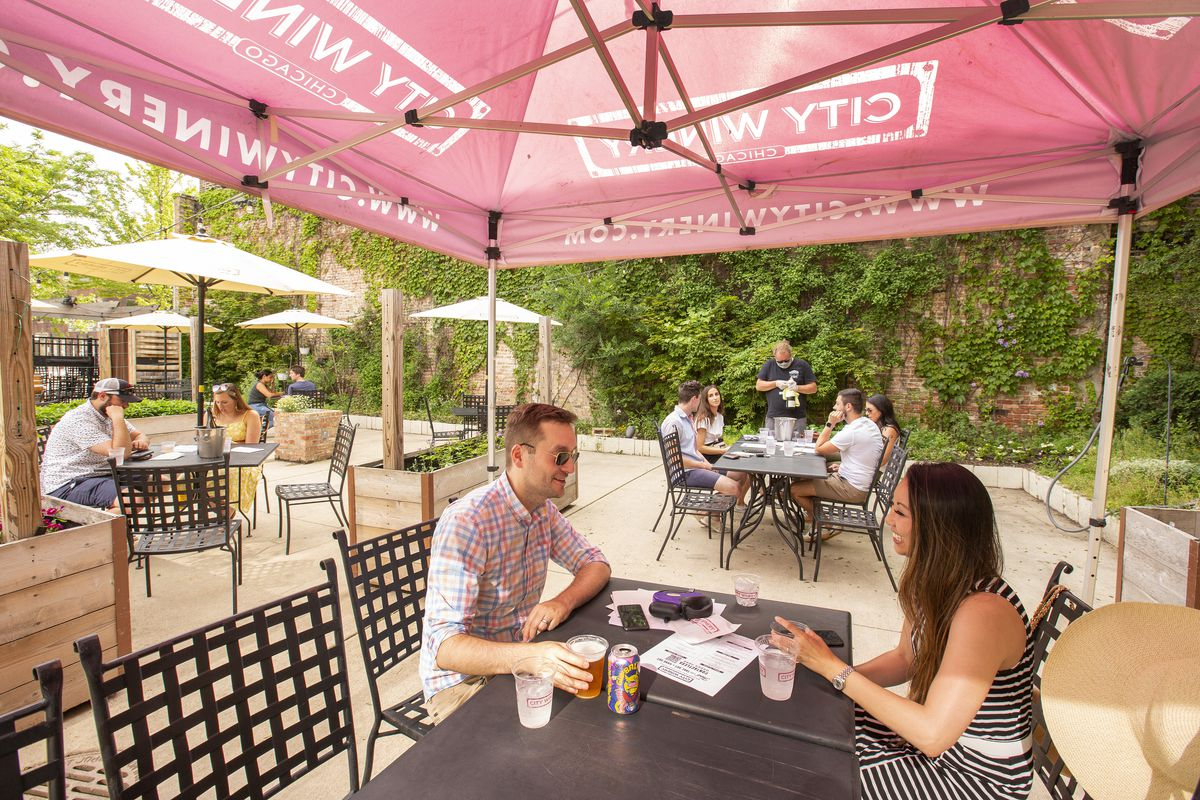 Customers sit at outdoor tables with drinks