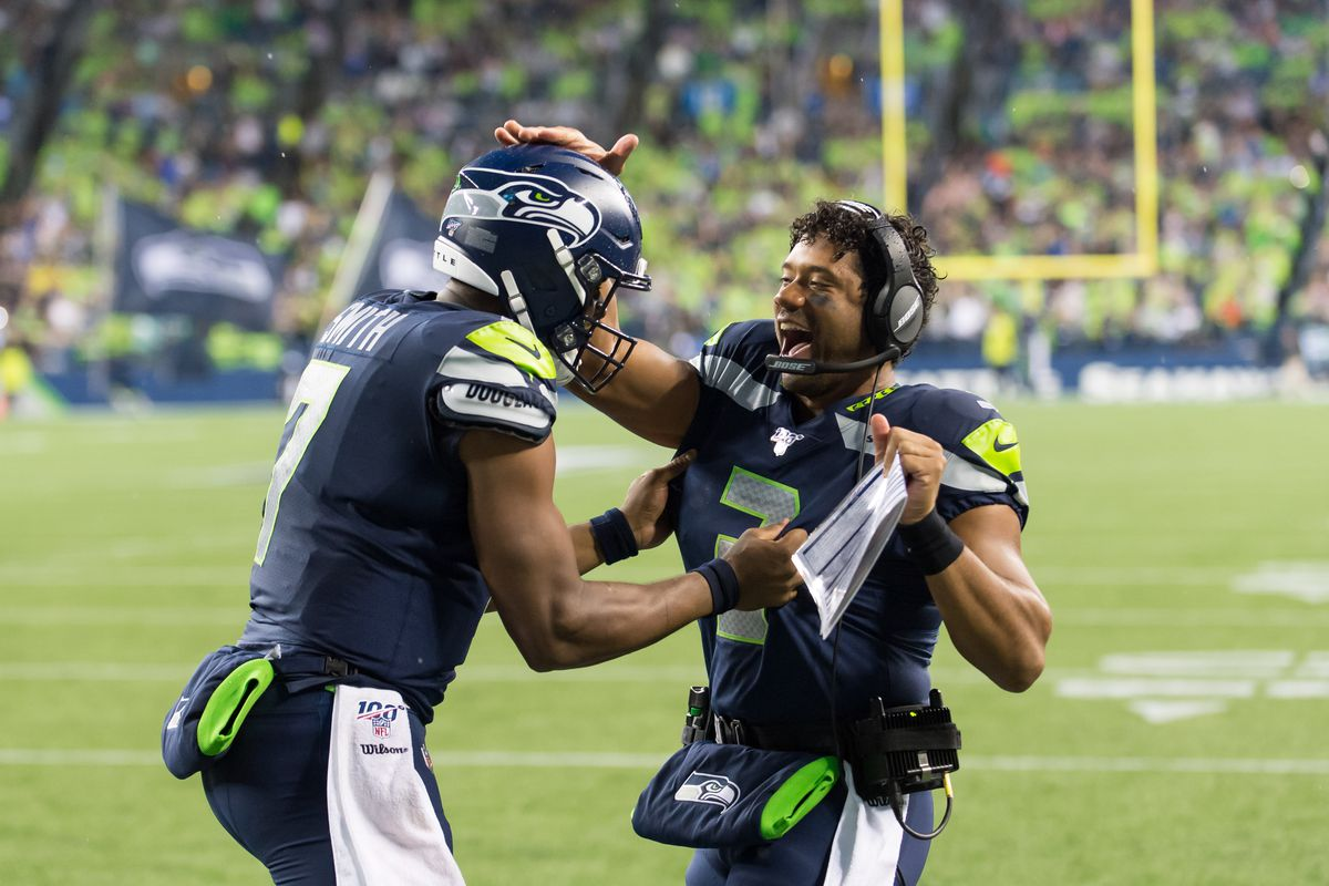 Seattle Seahawks quarterback Russell Wilson (3) celebrates with Seattle Seahawks quarterback Geno Smith (7) after Smith threw a pass for a touchdown against the Oakland Raiders during the first half at CenturyLink Field.